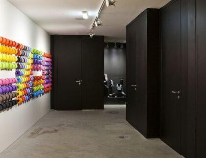drzwi wejściowe do kilku toalet oraz dziesiątki różnokolorowych rolek papieru toaletowego zawieszonych na ścianie