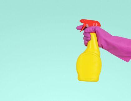 ręka w gumowej rękawicy trzymająca spray do mycia
